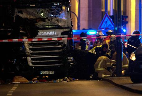 epa05682717 Rescue workers inspect the scenes and the truck that crashed into a Christmas market, close to the Kaiser Wilhelm memorial church in Berlin, Germany, 19 December 2016. According to the police, several people are reported killed and many injured in what police suspect it was a deliberate attack.  EPA/PAUL ZINKEN